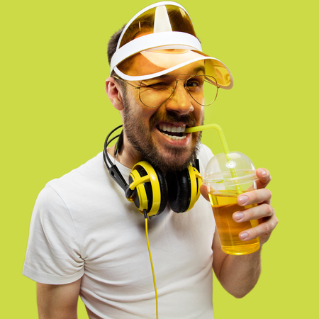 Half-length close up portrait of young man in shirt on yellow background. Male model with headphones and drink. The human emotions, facial expression, summer, weekend concept. Smiling and drinking. Stock Photo