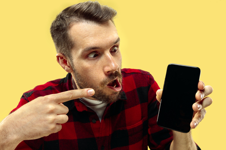 Half-length close up portrait of young man in shirt on yellow background. The human emotions, facial expression concept. Trendy colors. Negative space. Astonished and crazy. Showing a smartphone. Stock Photo