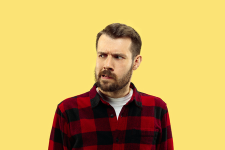 Half-length close up portrait of young man in shirt on yellow background. The human emotions, facial expression concept. Front view. Trendy colors. Negative space. Serious and thoughtful looking. Stock Photo
