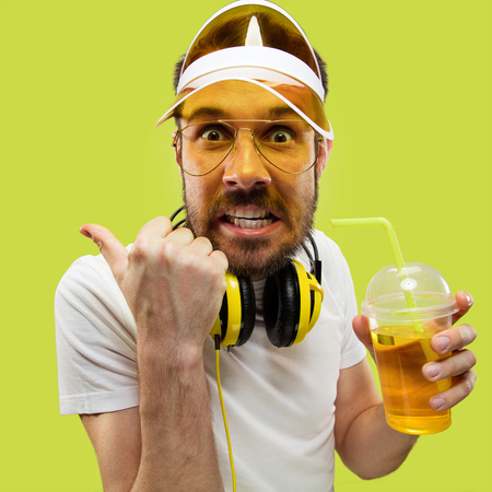 Half-length close up portrait of young man in shirt on yellow background. Male model with headphones and drink. The human emotions, facial expression, summer, weekend concept. Pointing for hurry up.