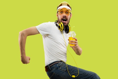 Half-length close up portrait of young man in shirt on yellow background. Male model with headphones and drink. The human emotions, facial expression, summer, weekend concept. Run for adventures.