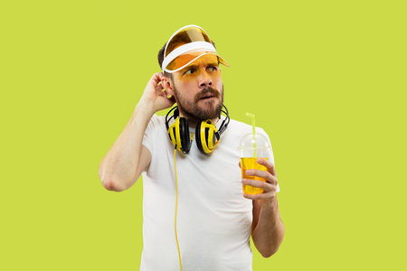 Half-length close up portrait of young man in shirt on yellow background. Male model with headphones and drink. The human emotions, facial expression, summer, weekend concept. Serious and thoughtful. Stock Photo