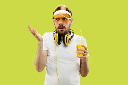 Half-length close up portrait of young man in shirt on yellow background. Male model with headphones and drink. The human emotions, facial expression, summer, weekend concept. Asking and thoughtful.