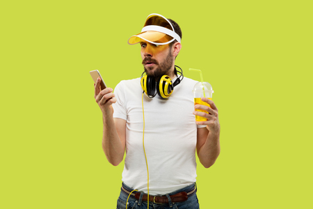 Half-length close up portrait of young man in shirt on yellow background. Male model with headphones and drink. The human emotions, facial expression, summer, weekend concept. Using smartphone.