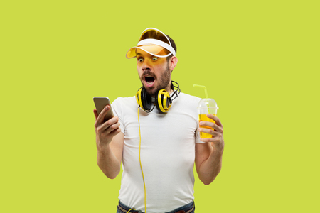 Half-length close up portrait of young man in shirt on yellow background. Male model with headphones and drink. The human emotions, facial expression, summer, weekend concept. Shocking news.