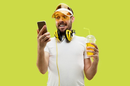 Half-length close up portrait of young man in shirt on yellow background. Male model with headphones and drink. The human emotions, facial expression, summer, weekend concept. Getting good news. Stock Photo