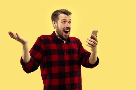 Half-length close up portrait of young man in shirt on yellow background. The human emotions, facial expression concept. Front view. Trendy colors. Negative space. Getting crazy of news in smartphone.