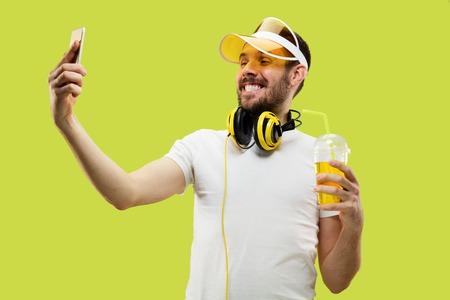 Half-length close up portrait of young man in shirt on yellow background. Male model with headphones and drink. The human emotions, facial expression, summer, weekend concept. Making selfie. Stock Photo