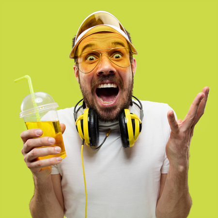 Half-length close up portrait of young man in shirt on yellow background. Male model with a drink. The human emotions, facial expression, summer, weekend concept. Getting crazy of happiness.
