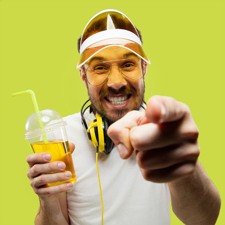 Half-length close up portrait of young man in shirt on yellow background. Male model with headphones and drink. The human emotions, facial expression, summer, weekend concept. Pointing and smiling. Stock Photo