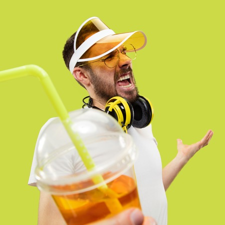 No doubts, come on. Half-length close up portrait of young man in shirt on yellow background. Male model with headphones and drink. The human emotions, facial expression, summer, weekend concept.
