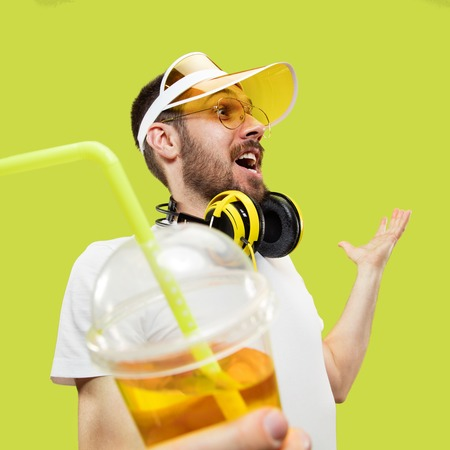 Happy meeting. Half-length close up portrait of young man in shirt on yellow background. Male model with headphones and drink. The human emotions, facial expression, summer, weekend concept.