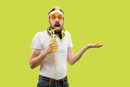 Half-length close up portrait of young man in shirt on yellow background. Male model with headphones and drink. The human emotions, facial expression, summer, weekend concept. Astonished and surprised.