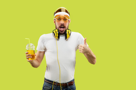 Half-length close up portrait of young man in shirt on yellow background. Male model with headphones and drink. The human emotions, facial expression, summer, weekend concept. Showing sign of OK. Stock Photo