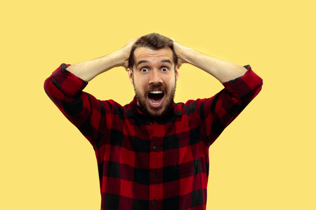 Half-length close up portrait of young man in shirt on yellow background. The human emotions, facial expression concept. Trendy colors. Astonished and crazy screaming while holding his head.