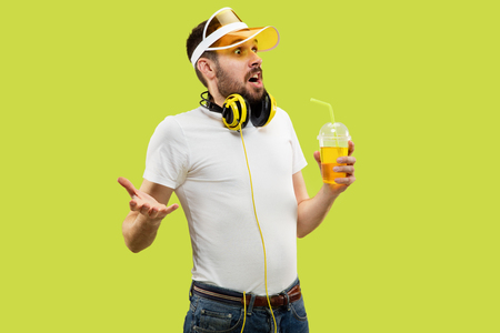 Half-length close up portrait of young man in shirt on yellow background. Male model with headphones and drink. The human emotions, facial expression, summer, weekend concept. Astonished and asking.
