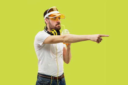 Half-length close up portrait of young man in shirt on yellow background. Male model with headphones and drink. The human emotions, facial expression, summer, weekend concept. Pointing and choosing.