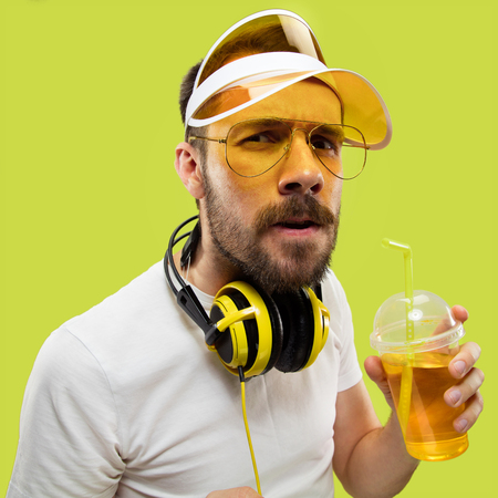 Half-length close up portrait of young man in shirt on yellow background. Male model with headphones and drink. The human emotions, facial expression, summer, weekend concept. Getting serious.