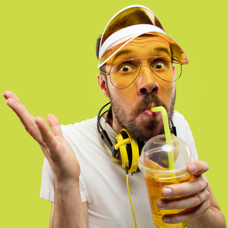 Half-length close up portrait of young man in shirt on yellow background. Male model with headphones and drink. The human emotions, facial expression, summer, weekend concept. Drinking funny.