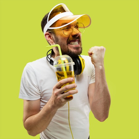 Half-length close up portrait of young man in shirt on yellow background. Male model with headphones and drink. The human emotions, facial expression, summer, weekend concept. Celebrating and rejoicing.