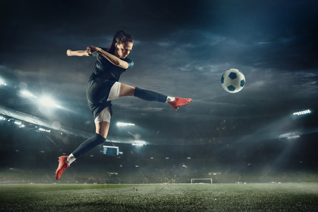 Young female soccer or football player with long hair in sportwear and boots kicking ball for the goal in jump at the stadium. Concept of healthy lifestyle, professional sport, hobby, motion, movement.