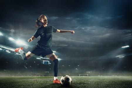 Giovane calciatrice o calciatrice con i capelli lunghi in abbigliamento sportivo e stivali che calcia la palla per l'obiettivo nel salto allo stadio. Concetto di stile di vita sano, sport professionistico, hobby, movimento, movimento.