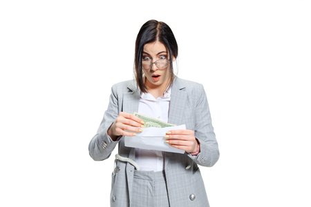 I hope its just a joke. Young woman in grey suit getting a small salary and not believing her eyes. Shocked and outraged. Concept of office workers troubles, business, problems and stress. Stock Photo