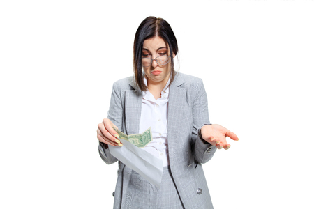 Its so many things Ill buy, yeah. Young woman in grey suit getting a small salary and not believing her eyes. Shocked and outraged. Concept of office workers troubles, business, problems and stress.
