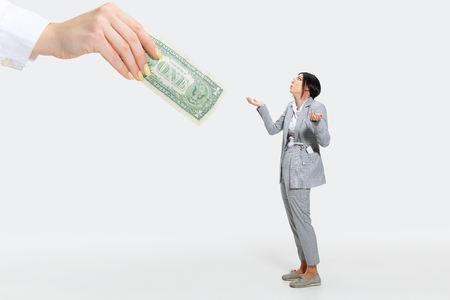Leave it for yourself, please. Young woman in grey suit getting a small salary and not believing her eyes. Shocked and outraged. Concept of office workers troubles, business, problems and stress. Stock Photo