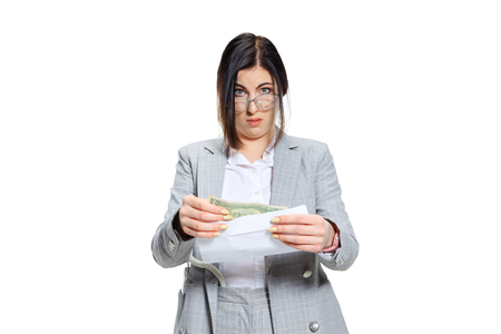 Is that the worldwide joking day. Young woman in grey suit getting a small salary and not believing her eyes. Shocked and outraged. Concept of office workers troubles, business, problems and stress.