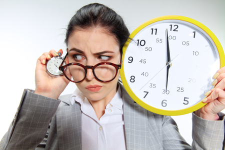 Young woman cant wait to go home from the nasty office. Holding the clock and waiting five minutes before the end. Concept of office workers troubles, business or problems with mental health. Stock Photo