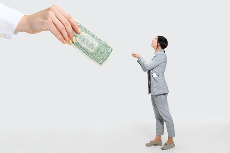 The smallest earnings in history. Young woman in grey suit getting a small salary and not believing her eyes. Shocked and outraged. Concept of office workers troubles, business, problems and stress.