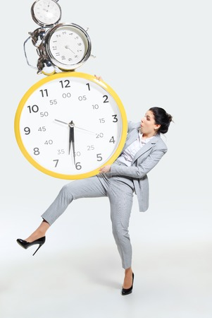 Young woman cant organize her worktime. Forced to constantly stay and work longer. Holding the big clock, has no time. Concept of office workers troubles, business or problems with mental health.