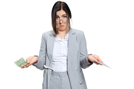No time for jokes, boss. Young woman in grey suit getting a small salary and not believing her eyes. Shocked and outraged. Concept of office workers troubles, business, problems and stress. Stock Photo