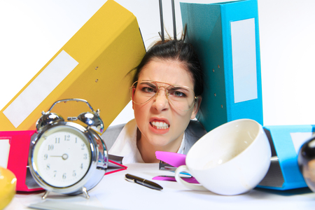 Really angry. Young woman getting a lot of work and deadline, being under the pressure of the deals. Pressed by folders with papers. Concept of office workers troubles, business, problems and stress. Imagens