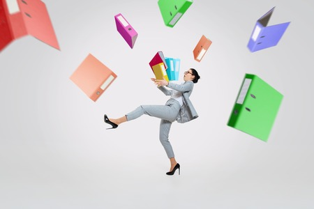 Young woman in suit getting a lot of work and losing concentration. Dropping folders with papers on the go, trying to catch that. Concept of office workers troubles, business, problems and stress.