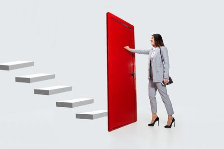 Bussare nel vuoto. Giovane donna in abito grigio che cerca di aprire la porta rossa nella scala della carriera, ma è chiusa. Nessun modo per la motivazione. Concetto di problemi degli impiegati, affari, problemi, stress.