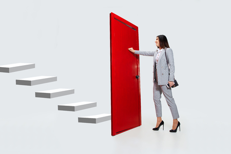 Knocking in emptiness. Young woman in grey suit trying to open the red door in career ladder, but its closed. No way for motivation. Concept of office workers troubles, business, problems, stress.