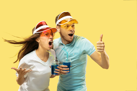 Beautiful young couples half-length portrait isolated on yellow studio background. Woman and man standing with drinks in colorful caps. Facial expression, summer, weekend concept. Trendy colors. 版權商用圖片