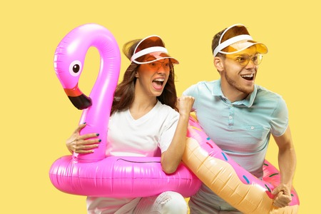 Beautiful young couples half-length portrait isolated on yellow studio background. Woman and man in caps and sunglasses standing with swimming rings. Facial expression, summer, weekend concept.