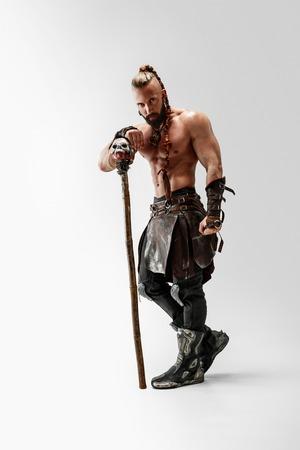 Grave pelo largo y modelo masculino musculoso en traje de vikingos de cuero con la gran maza cosplaying aislado sobre fondo blanco de estudio. Retrato de cuerpo entero. Guerrero de fantasía, antiguo concepto de batalla.