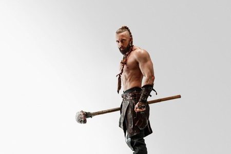 Serious long hair and muscular male model in leather vikings costume with the big mace cosplaying isolated on white studio background. Half-length portrait. Fantasy warrior, antique battle concept. Stock Photo