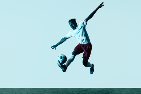 Young african-american male football or soccer player in sportwear and boots kicking ball for the goal in neon light isolated on white background. Concept of healthy lifestyle, professional sport, hobby.