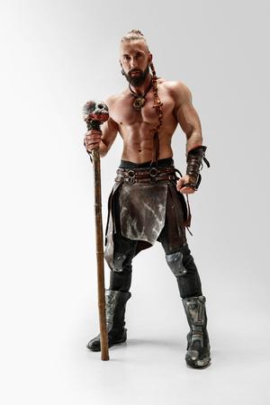 Poważne długie włosy i muskularny męski model w skórzanym stroju wikingów z dużą maczugą cosplaying na białym tle studio. Portret pełnometrażowy. Wojownik fantasy, koncepcja antyczne bitwy. Zdjęcie Seryjne