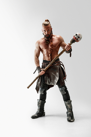 Serious long hair and muscular male model in leather vikings costume with the big mace cosplaying isolated on white studio background. Full-length portrait. Fantasy warrior, antique battle concept. Reklamní fotografie
