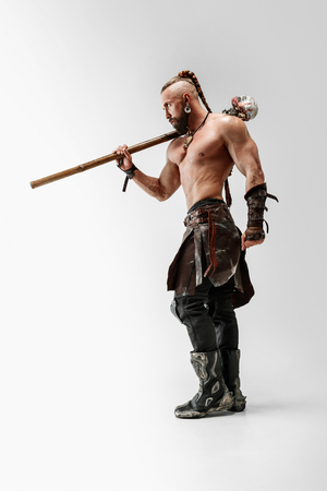 Serious long hair and muscular male model in leather vikings costume with the big mace cosplaying isolated on white studio background. Full-length portrait. Fantasy warrior, antique battle concept. Stock Photo
