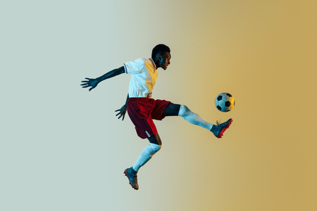 Young african-american male football or soccer player in sportwear and boots kicking ball for the goal in jump in neon light on gradient background. Concept of healthy lifestyle, professional sport.
