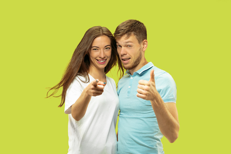Beautiful young couples half-length portrait isolated on green studio background. Woman and man standing and pointing up, showing the sing of OK. Facial expression, human emotions concept.