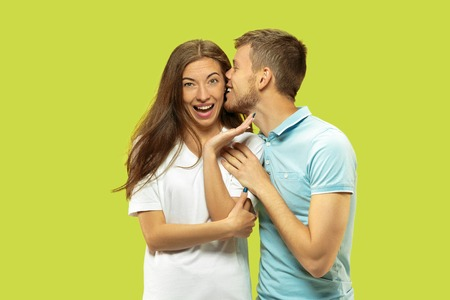 Beautiful young couples half-length portrait isolated on green studio background. Woman and man standing, caddling and kissing . Facial expression, human emotions concept. Trendy colors. 免版税图像