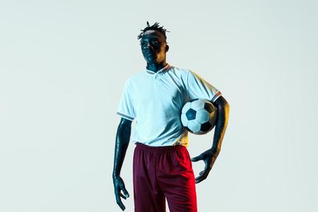 Giovane giocatore di calcio o di calcio maschio afroamericano in abbigliamento sportivo e stivali in piedi con la palla alla luce al neon isolato su sfondo bianco. Concetto di stile di vita sano, sport professionistico, hobby.